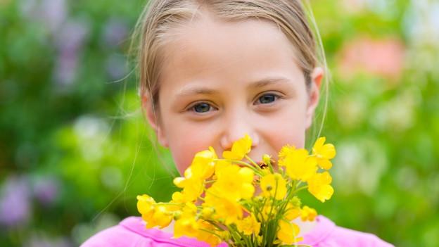 Mädchen riecht an gelben Blumen.