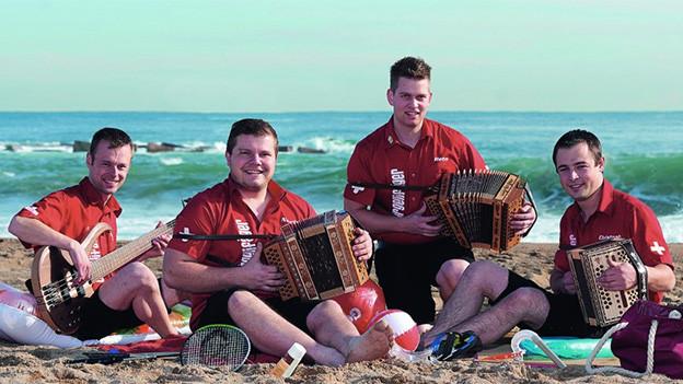 Vier Volksmusikanten sitzen mit ihren Instrumenten am Strand.