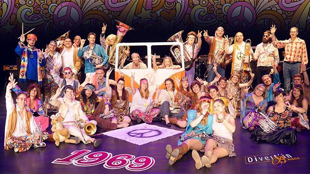 Junge Musikantinnen und Musikanten im Hippie-Look auf einer Bühne.