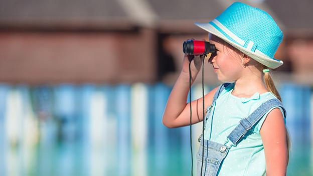 Ein Mädchen mit rotem Strohhut blickt durch ein Fernglas.