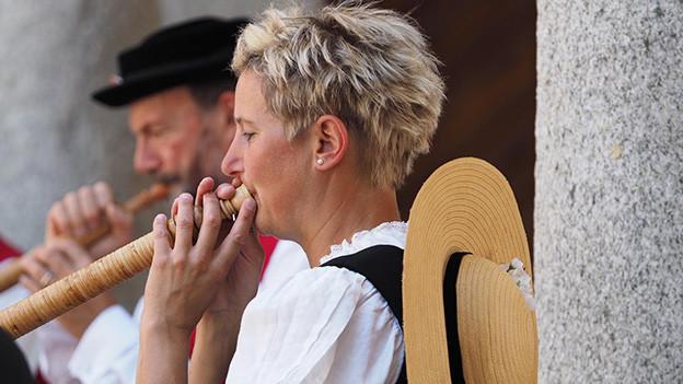 Ein Mann und eine Frau spielen Alphorn.