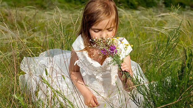 Ein Mädchen in einem weissen Sommerkleid sitzt in einer Sommerwiese.