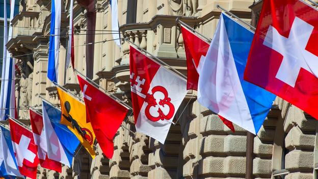 Schweizer Kantonsfahnen hängen an Hauswand.