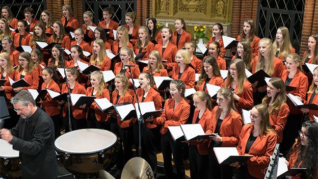 Ein Chor mit jungen Sängerinnen in roten Blusen.