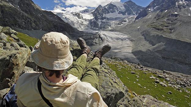Eine Wanderin sitzt mit ausgestreckten Beinen mitten in der Bergwelt.