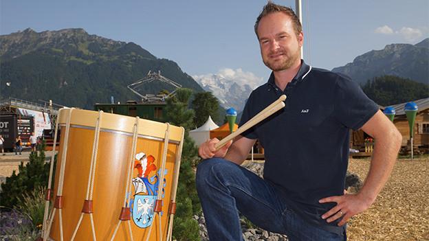 Ein Tambourspieler vor einer Bergkulisse.