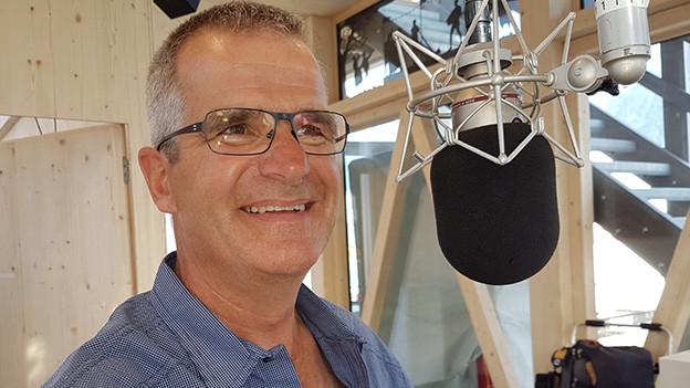 Ein Mann mit Brille steht lachend hinter einem Mikrofon.