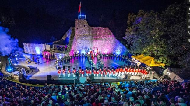 Illuminierte Burgruine mit Zuschauertribüne und Militärmusik.