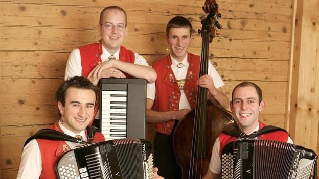 Vier Volksmusiker vor Holzwand.