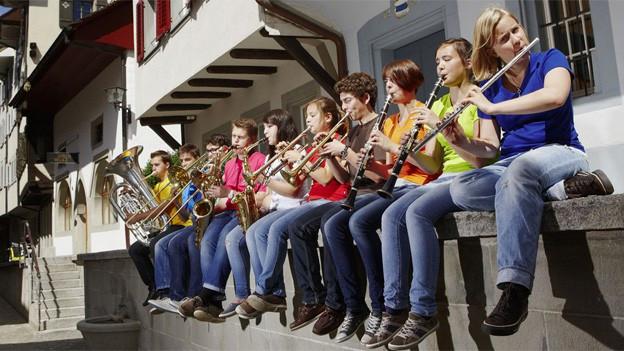 Jugendliche mit Blasmusikinstrumenten sitzten nebeneinander auf einer Mauer.