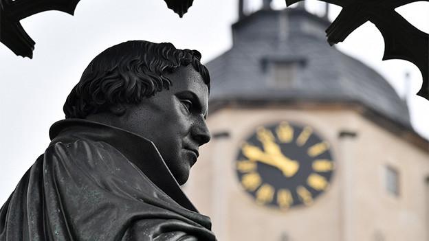 Ein Denkmal mit Blick auf eine Kirchenuhr.