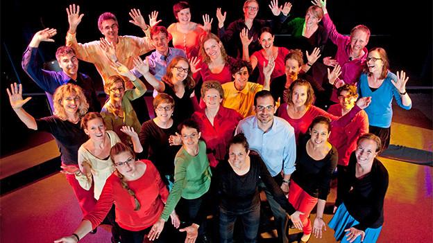 Gruppenbild mit bunt gekleideten Sängerinnen und Sängern.