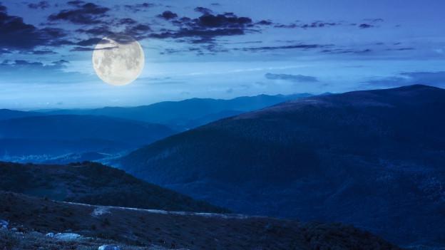 Berge und Vollmond getunkt in mystisches Blau.