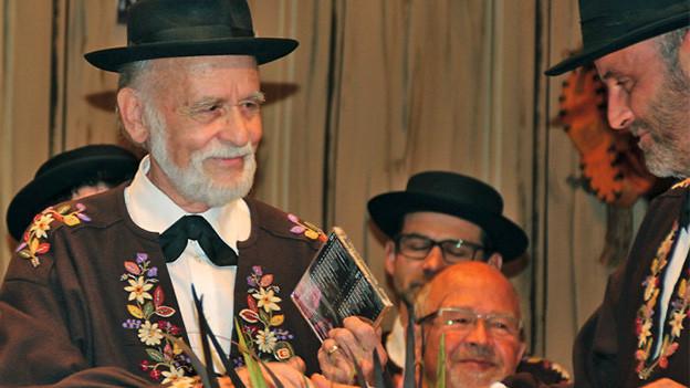 Ein Mann im braunen Sennenhemd vor einem Rednerpult.