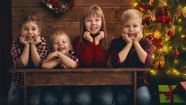 Vier Kinder sitzen lachend an einem Tisch neben einem Weihnachtsbaum.