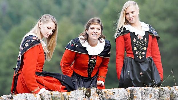 Drei junge Trachtenfrauen auf einer grünen Wiese.