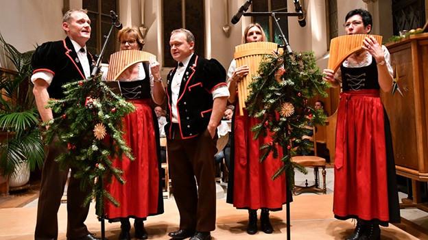 Zwei Jodler und drei Bambusflötenspielerinnen in einer Kirche.