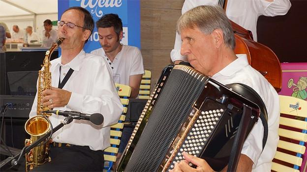 Zwei Volksmusikanten spielen Klarinette und Akkordeon.