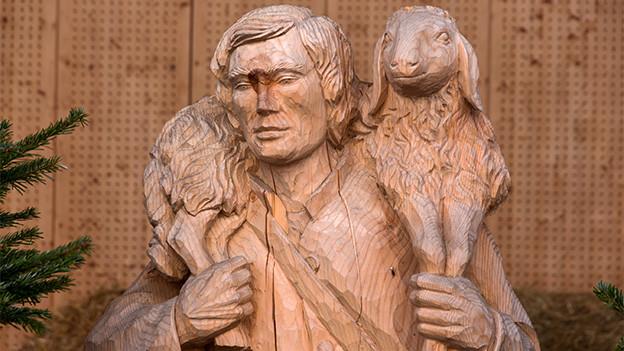 Ein Hirte aus Holz, der ein Schaf über den Schultern trägt.