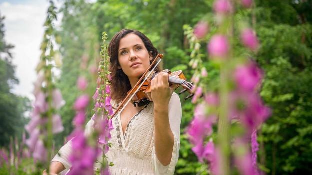 Frau mit Geige auf Wiese mit lilafarbenen Gräsern.