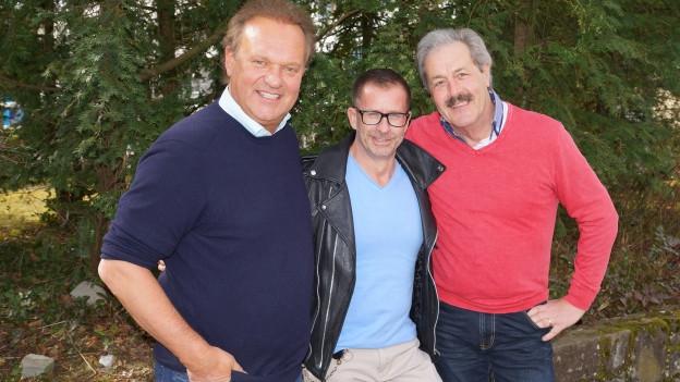 Drei Männer im Garten.