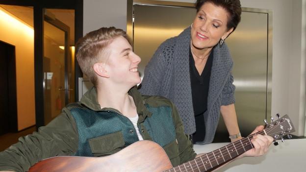 Junger Sänger mit Gitarre auf Bank, daneben Maja Brunner.