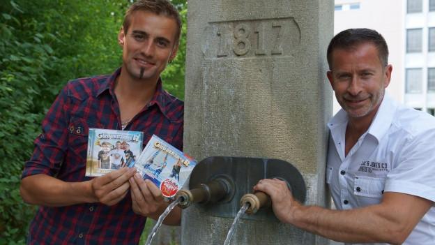 Zwei Männer vor Brunnen.