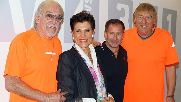 Gruppenbild im Radiostudio mit zwei sitzenden Männern und einer Frau, die dazwischen steht.