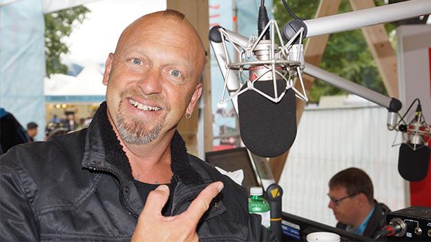 Der Sänger zeigt lachend auf ein Mikrofon.