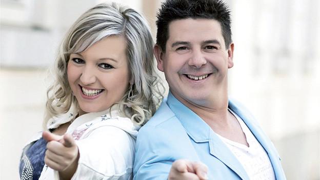 Eine blondhaarige Frau und ein dunkelhaariger Mann lachen frisch in die Kamera.