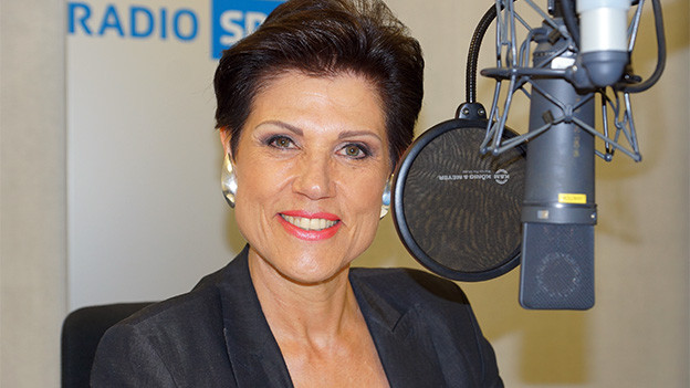 Eine Moderatorin hinter dem Mikrofon.