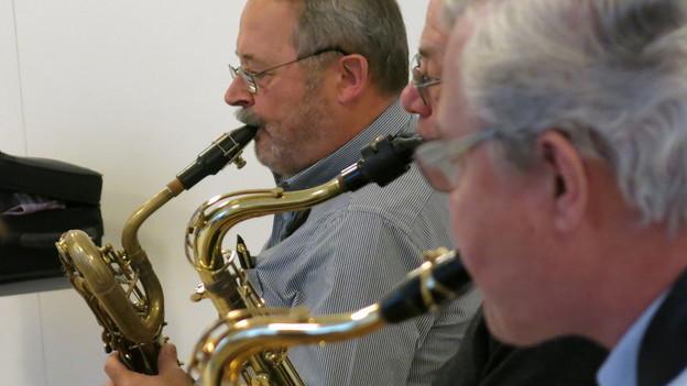 Drei ältere Männer spielen Saxofon.