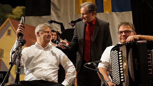 Ein Moderator unterhält sich mit Musikanten, die mit ihren Instrumenten auf einer Bühne sitzen.