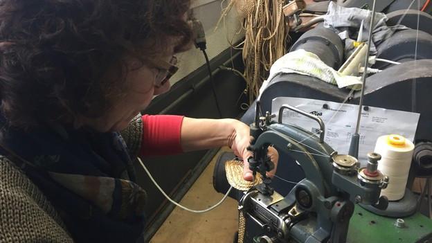 Eine Strohhut-Macherin in einer Werkstatt.