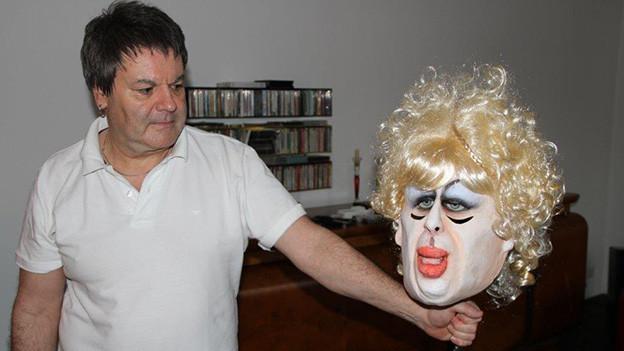 Ein Mann zeigt eine selbst gefertigte Maske mit stark geschminktem Gesicht und blonden Haaren.