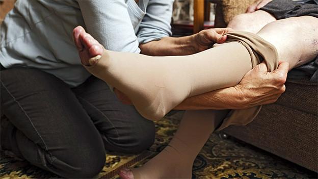 Eine Frau kniet auf dem Boden und zieht einer älteren Frau Stützstrümpe an.