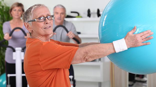 Eine ältere Frau mit Brille hält mit ausgestreckten Armen einen grossen Sitzball.