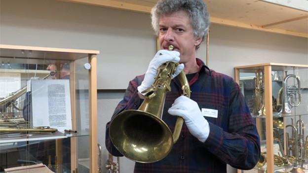 Ein Mann mit einem Klappenflügelhorn in einem Ausstellungsraum voller Instrumente.