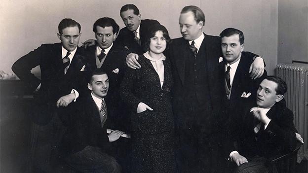 Schwarz-Weiss-Fotografie mit einer Dame, umgeben von sieben Männern.