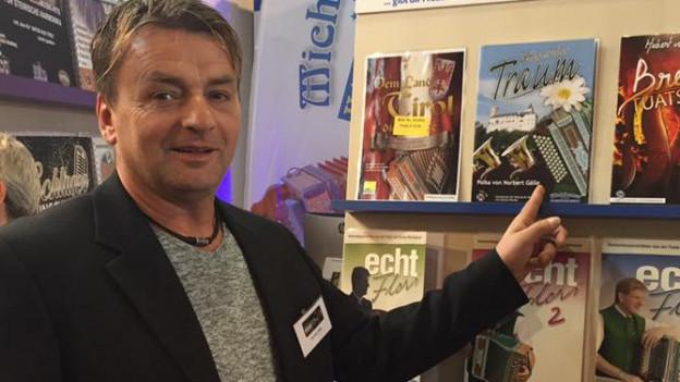 Mann zeigt auf Verkaufsstand mit CD.