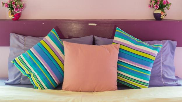 Bett mit bunten Kissen.