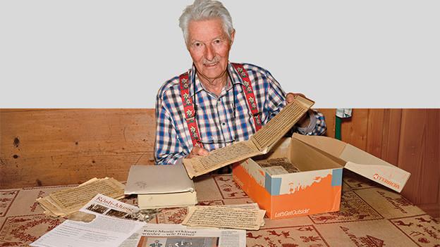 Ein ältere Mann sitzt an einem Tisch, auf dem verschiedene Dokumente ausgelegt sind.