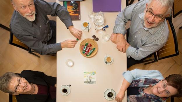 Seniorinnen und Senioren gemeinsam an einem Tisch.