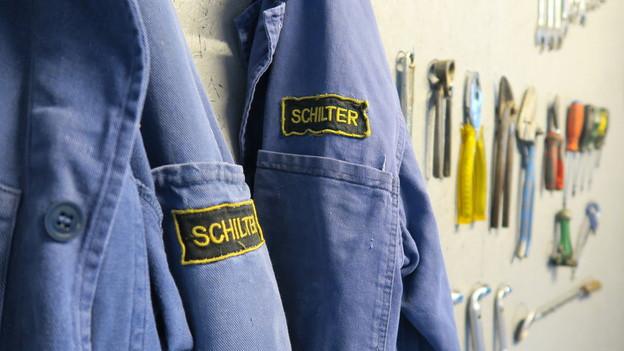 Blaue Arbeiterjacken hängen neben verschiedenen Werkzeugen.