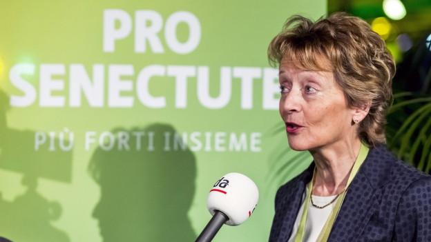 Eveline Widmer-Schlumpf mit Mikrofon vor Plakat der Pro Senectute.