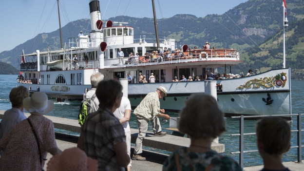 Blick von der Anlegestelle am See auf ein Schiff.