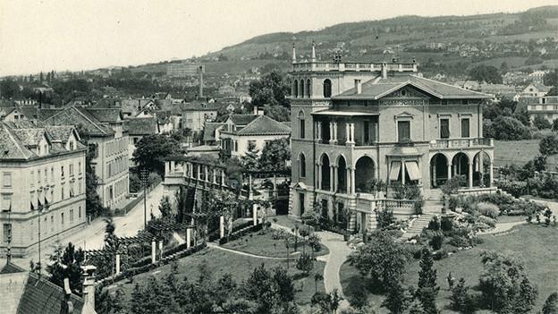 Schwarz-Weiss-Fotografie einer stattlichen Villa, umgeben von einer grossen Parkanlage.