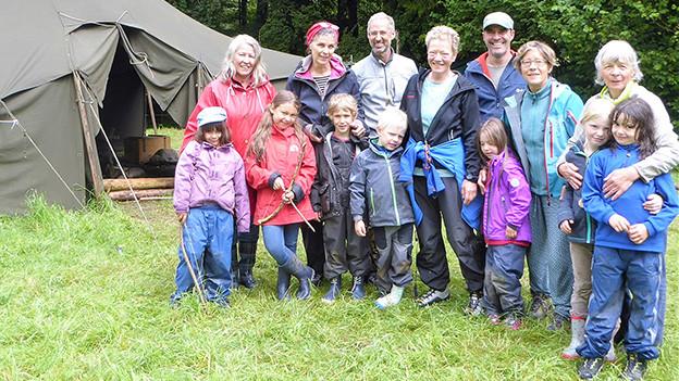 Eine Gruppe von jungen und älteren Menschen vor einem Zelt.