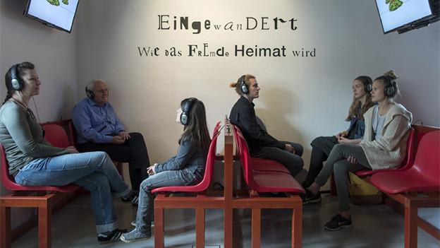 Verschiedene Menschen mit Kopfhörern in einem Ausstellungsraum.