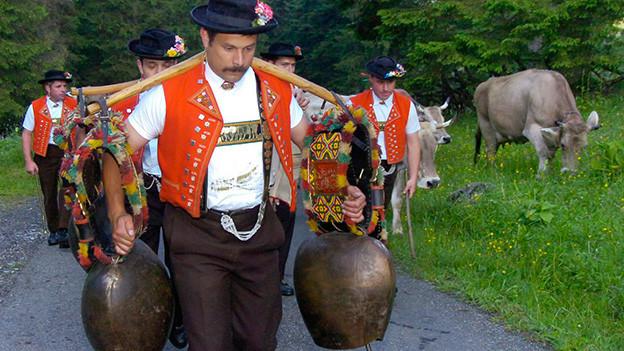 Ein Senn in Appenzellertracht trägt eine Holzstange mit zwei grossen Schellen über den Schultern.